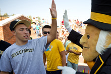 Wake Forest seniors high-five the Deacon at a Winston-Salem Dash game.