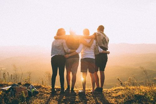 friends with arms around each other staring off into the sunset