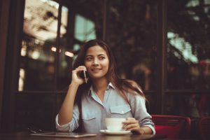 Photo of a woman drinking coffee while on her phone