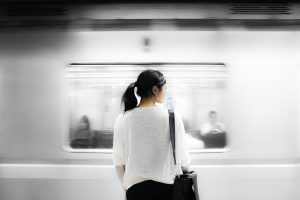 Woman standing while subway car zooms past her in the background