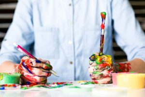 Man who is writing and painting with many different paint colors all over his hands