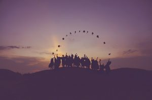 graduates on a hill at sunset throwing their graduation hats