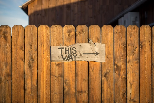 """Wood fence with a sign that says """"This way"""" with an arrow pointing to the right"""