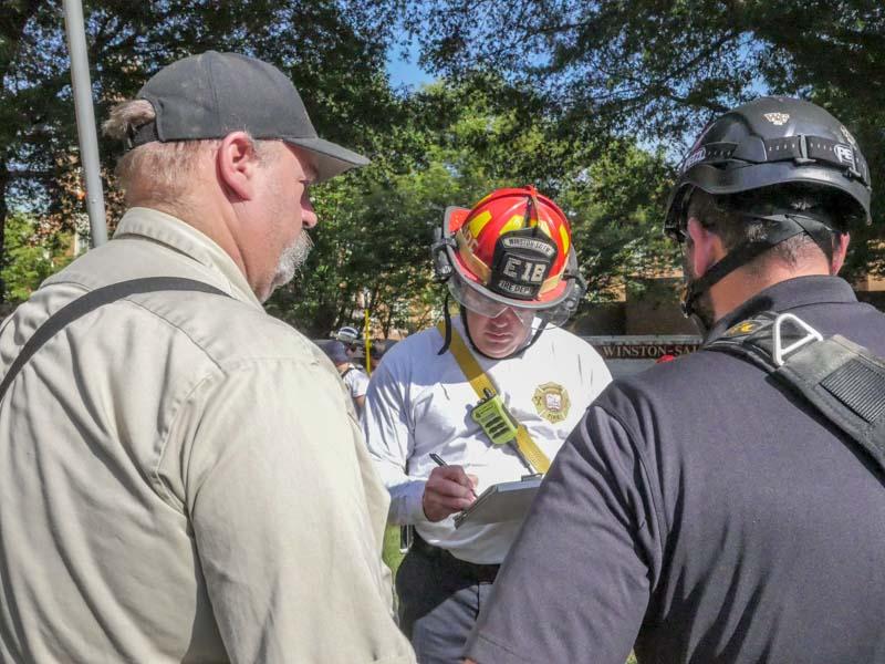 firefighter rescue team gets scenario info from WFU employees for confined space training drill