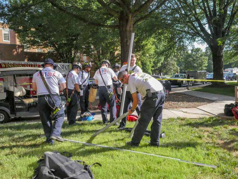 fire department team sets up equipment for confined space training drill