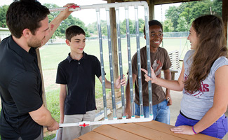 Graduate student Corey Hewitt and some of the students examine the HySterE solar panel that the students built.