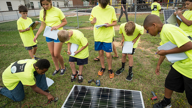 Hanes Middle School students attending the Power Up! summer camp, taught by Wake Forest physics faculty and graduate students, interact with the Hybrid Sterling Energy Generator (HySterE) panel.