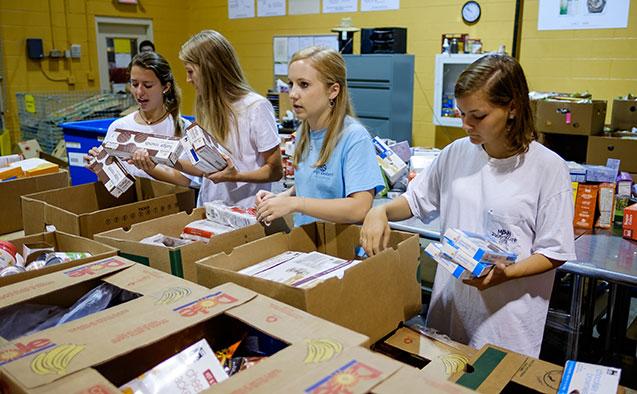 Students pack food at a food pantry