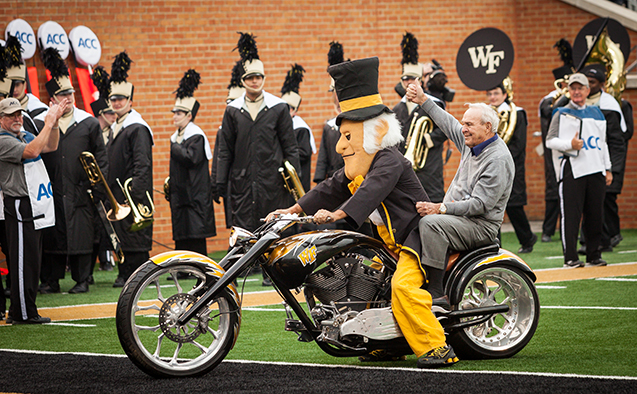 Arnold Palmer riding the motorcycle with the Demon Deacon