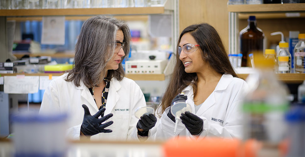 Rebecca Alexander, director of academic programming for Wake Downtown, works with Nisha Patel ('17) in her lab.
