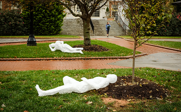 Tape cast 'people' travel around campus in 'flat Stanley'-style, sitting at picnic tables, under trees or on benches