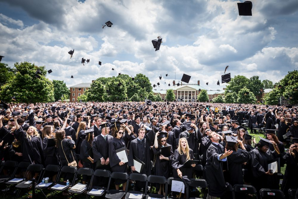 New graduates toss their mortarboards in celebration.