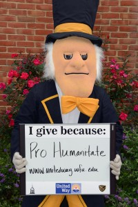 The Demon Deacon holds a sign that says Pro Humanitate